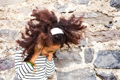 Beautiful african american girl with headphones, listening music.