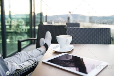Unrecognizable businessman with a tablet in rooftop cafe