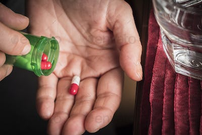 Women take white and red capsule with right hand from a green bottle