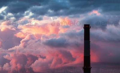 Industrial chimney stack silhouette against the background of the storm sky at sunset
