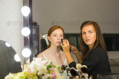 make up artist doing professional make up of young red-haired woman.