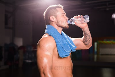 young caucasian bodybuilder in the gym drinking a bottle water.