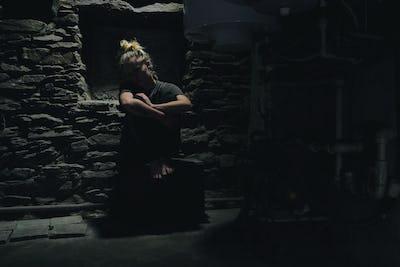 depressed anxious woman sitting in a dark corner of a basement