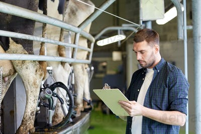 man with clipboard and milking cows on dairy farm