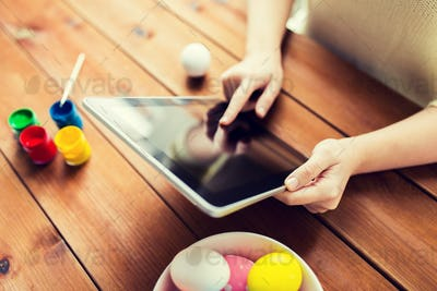 close up of woman with tablet pc and easter eggs