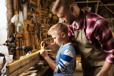 father and son with ruler measure wood at workshop