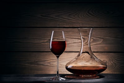 Decanter and glass with red wine on a wooden table