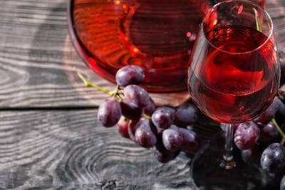 Wooden background with glass of red wine and a bunch of grapes