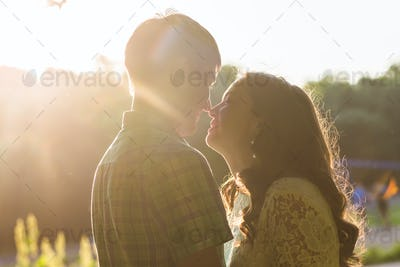 Closeup photo of romantic kissing couple outdoors, side view.