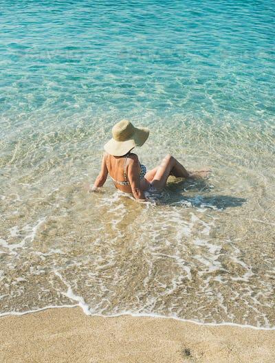 Senior woman tourist in bikini sitting at clear sea waters