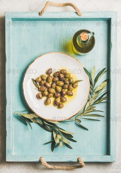 Pickled green Mediterranean olives, olive tree branch, virgin oil