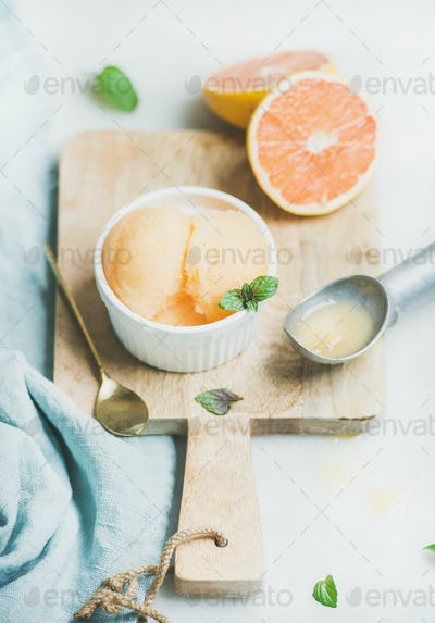 Pink grapefruit sorbet with fresh mint leaves in bowl