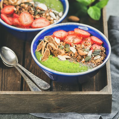 Green smoothie bowls with seeds, nuts and fruit, square crop