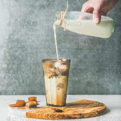 Man's hand pouring milk to Iced latte summer coffee cocktail