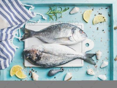 Fresh Sea bream raw uncooked fish with seasoning and lemon