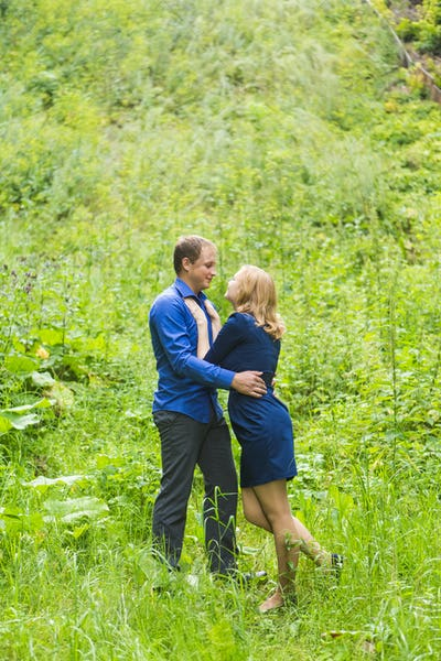 summer holidays, love, romance and people concept - happy smiling young couple hugging outdoors