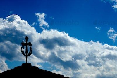 Cross on a monastery roof with a blue sky