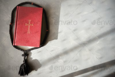 Bible and rosary on a cement background.