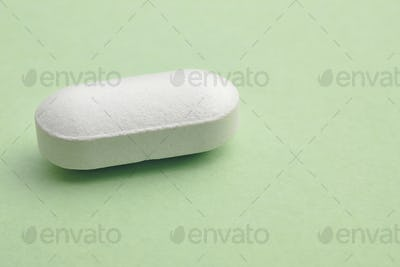 Pill over a green background. Medicament treatment. Health care photo