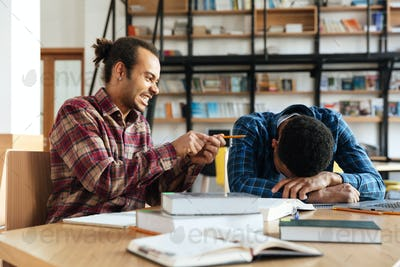 Young funny man student sitting in library near tired friend.