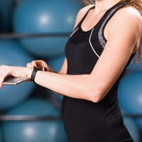 Close-up of female hands with fitness tracker and smartphone in gym