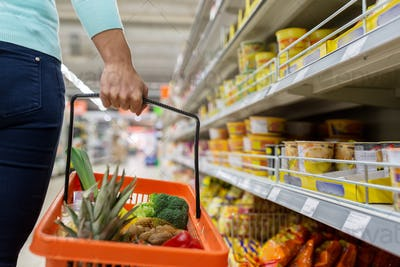 woman with food basket at grocery or supermarket