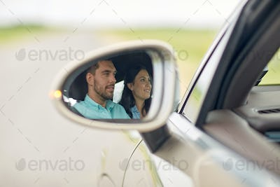 side mirror reflection of happy couple driving car