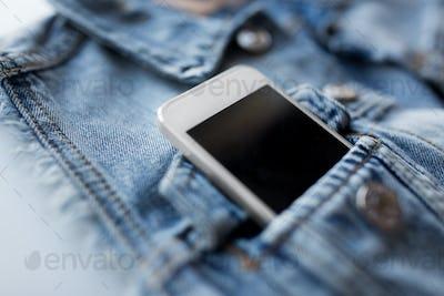 smartphone in pocket of denim jacket or waistcoat