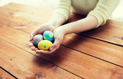close up of woman hands with colored easter eggs