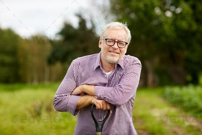 happy smiling senior man with garden tool at farm