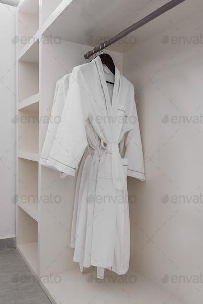 white bathrobe with wooden hangers in wardrobe