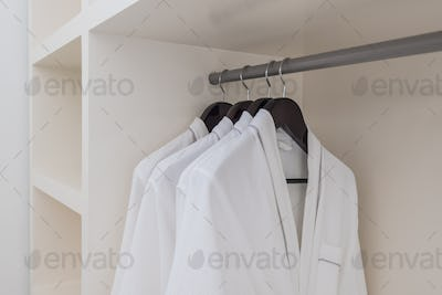 white bathrobe with wooden hangers in wardrobe