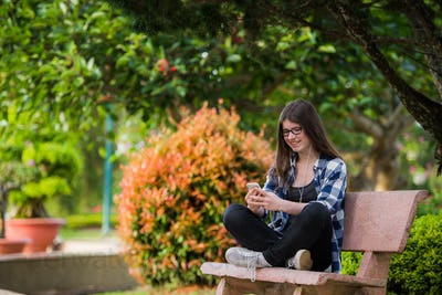 Teenage girl sitting on bench using phone and looking upset