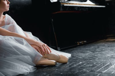 Young ballerina dancing, closeup on legs and shoes, sitting in pointe shooses