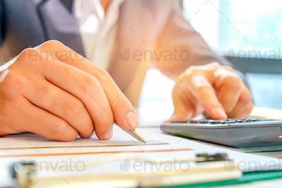 Businessmen are using a calculator and using a pen to analyze da