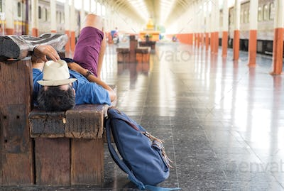 Travelers slept on chairs while waiting for the train,Hat on fac