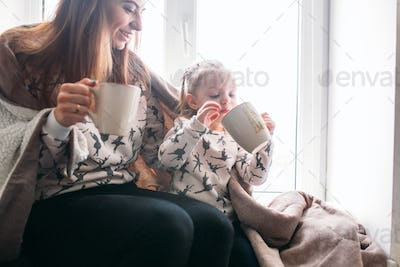 Mom and daughter drink something with mug