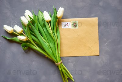 White tulips bouquet and postcard on grey background