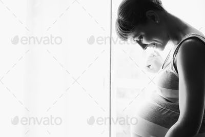 Young beautiful pregnant woman standing near window at home