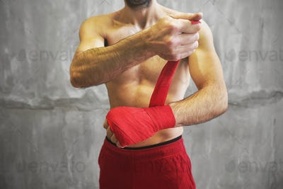 Man is wrapping hands with red boxing wraps.