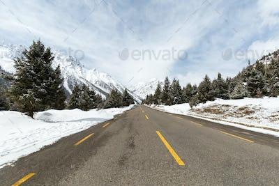 empty asphalt road between the snow mountain