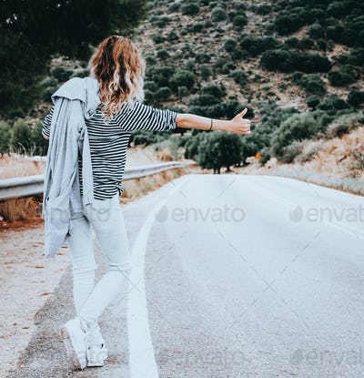 Woman hitchhiking along the road.