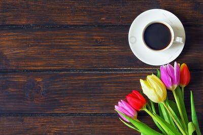 A cup of coffee, a bouquet of  tulips on a dark wooden table