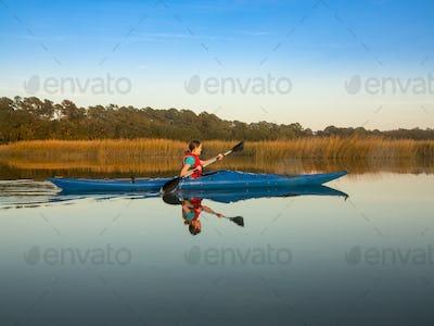 Teen kayaking through glassy water