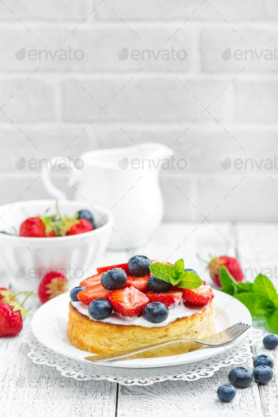 Delicious berry cheesecake with fresh strawberry and blueberry on white background
