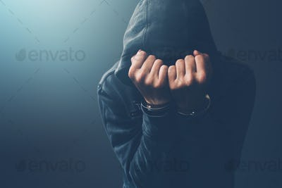 Arrested computer hacker with handcuffs wearing hooded jacket