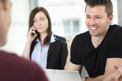 Young Businessman Smiling While Looking At Colleague