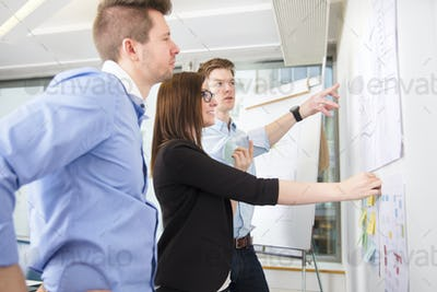 Business People Discussing Over Line Graph Stuck On Wall