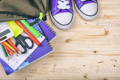 School backpack and supplies on wooden background