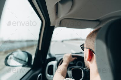 The man in the car traveling on the road